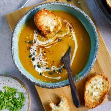 cremige vegane Kürbissuppe mit Kokosmilch und einem Stück Brot von oben