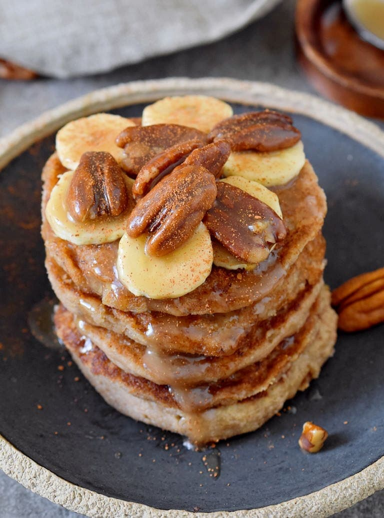 stack of pancakes with pecans and banana on a black plate