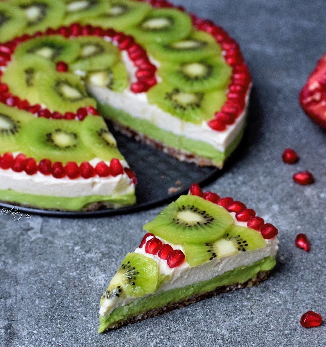 Vegan fruity cheesecake with an avocado and gluten-free cashew layer. Decorated with kiwi and pomegranate.