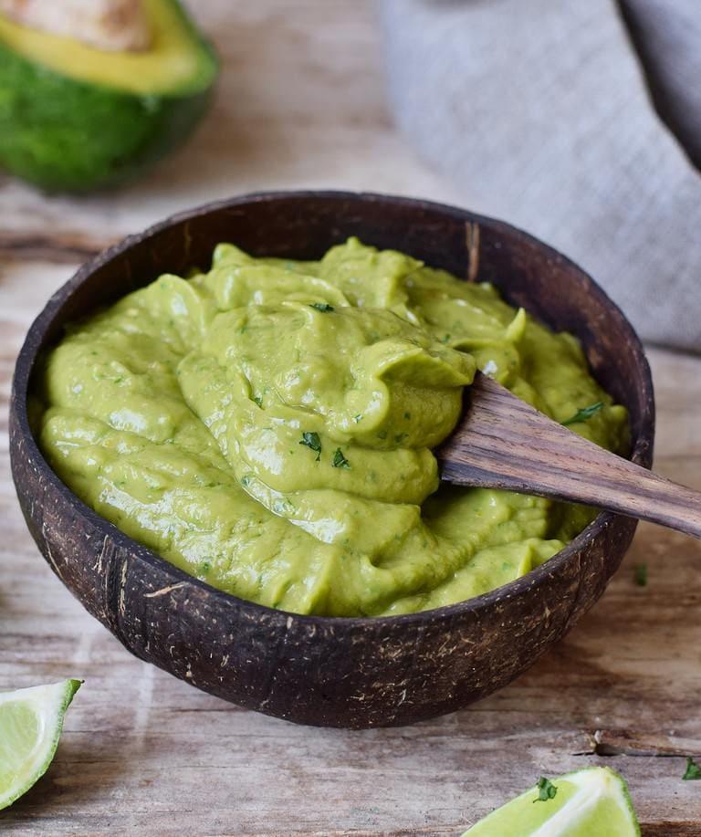 Creamy guacamole in a coconut bowl