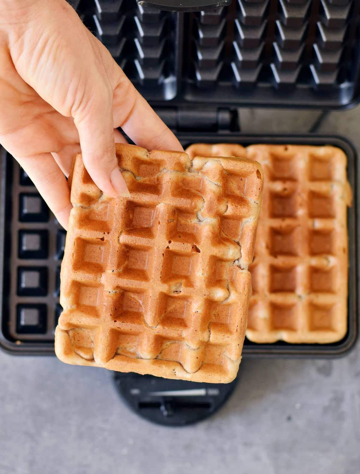 hand holding one vegan waffle