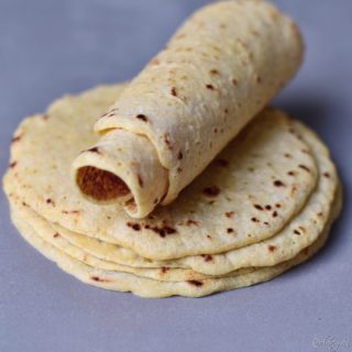 Homemade stack of gluten free tortillas with the top one rolled up
