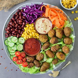 This healthy vegan lunch bowl with Hasselback potatoes is filling, easy to make and delicious. The buddha bowl is rich in plant-based protein, gluten-free and grain-free. Two easy and tasty sauce recipes included