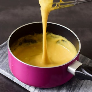 vegan cheese sauce in pink saucepan with cheese pull
