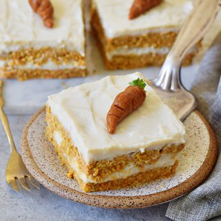 vegan cake with white cream and marzipan carrots on top