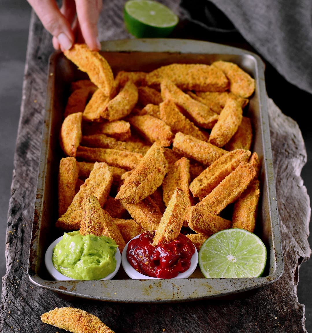Eating oven-baked vegan parmesan potato wedges with guacamole dip and ketchup