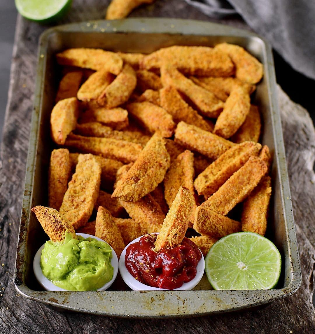 Crispy oven-baked vegan parmesan potato wedges with guacamole dip and ketchup