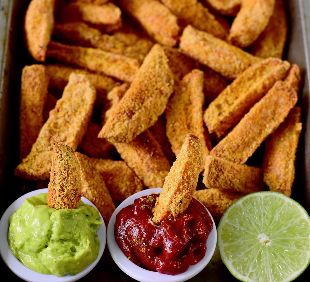 Close-up vegan parmesan potato wedges with guacamole dip and ketchup