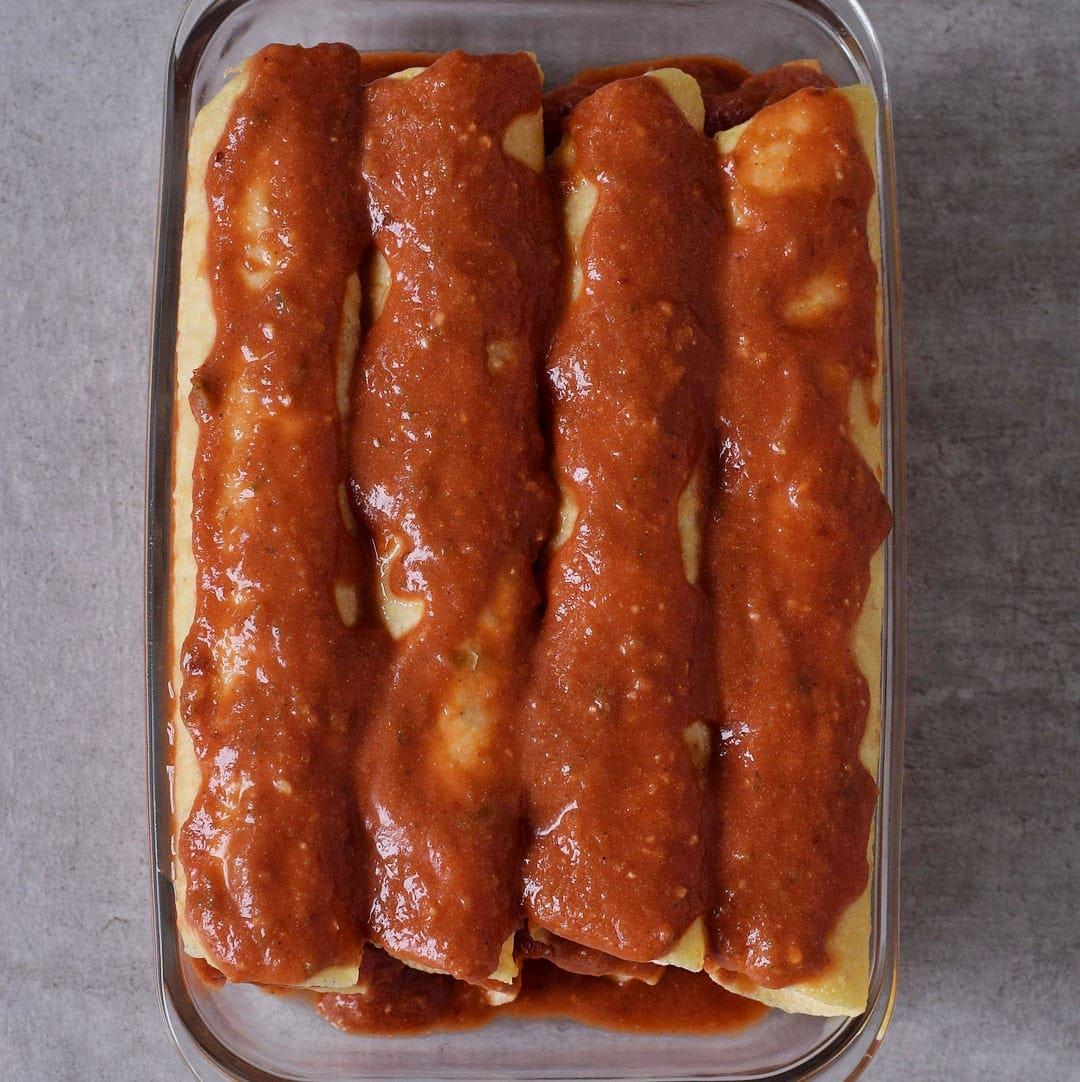 zusammengerollte Tortillas in Auflaufform mit Enchilada-Sauce