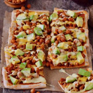 Avocado chickpea pizza cut into square pieces