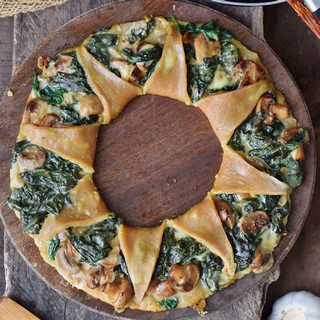 Pizza ring (pizza corona) with spinach mushrooms and vegan cheese sauce