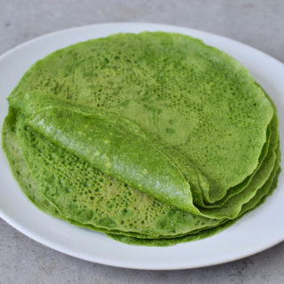 Stack of homemade spinach tortillas on a white plate