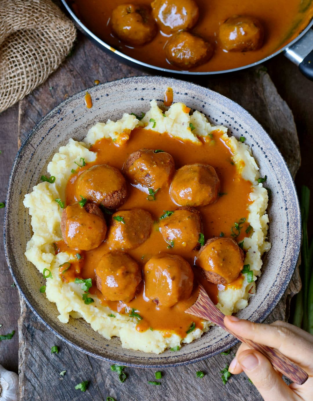 Eating gluten-free vegan meatballs with gravy and mashed potatoes