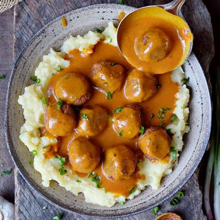 Hearty vegan meatballs with gluten-free gravy over mashed potatoes in a plate with ladle