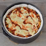 Vegan deep dish pizza gluten-free dough with veggies mushrooms and vegan cheese