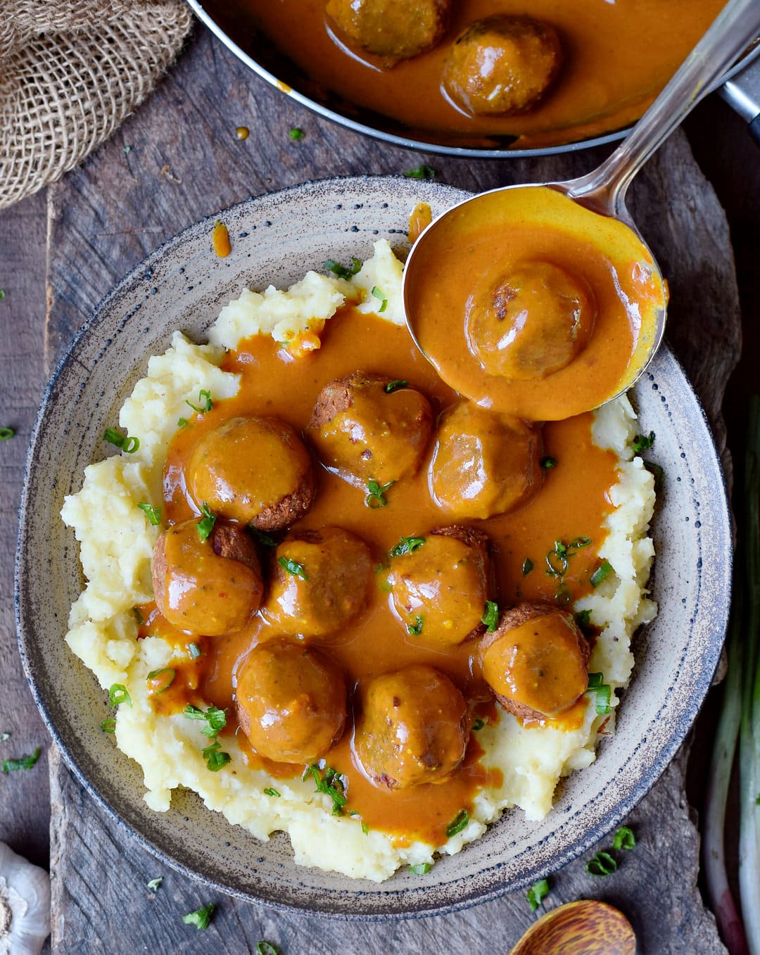 Vegan meatballs with gluten-free gravy over mashed potatoes in a plate with ladle