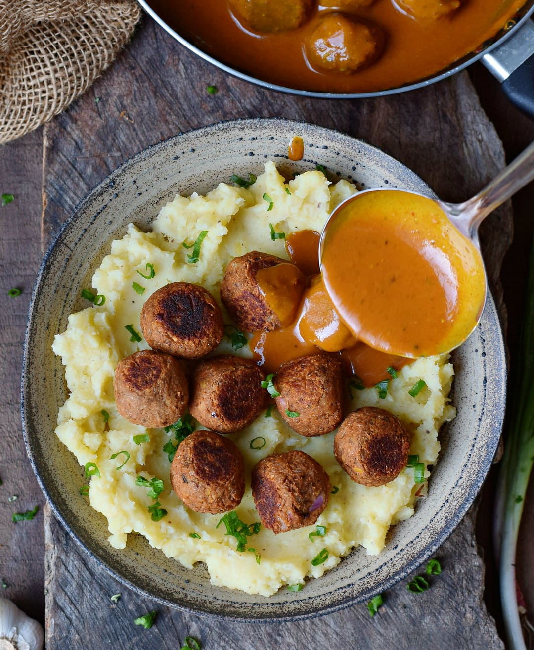 Vegan meatballs with gravy drizzle over mashed potatoes
