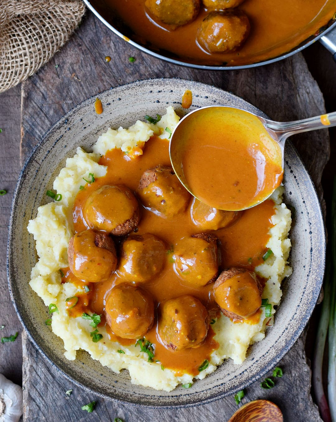 Vegan meatballs with hearty gravy in a ladle over mashed potatoes