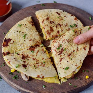 vegan quesadillas on a cutting board filled with plant-based cheese and veggies