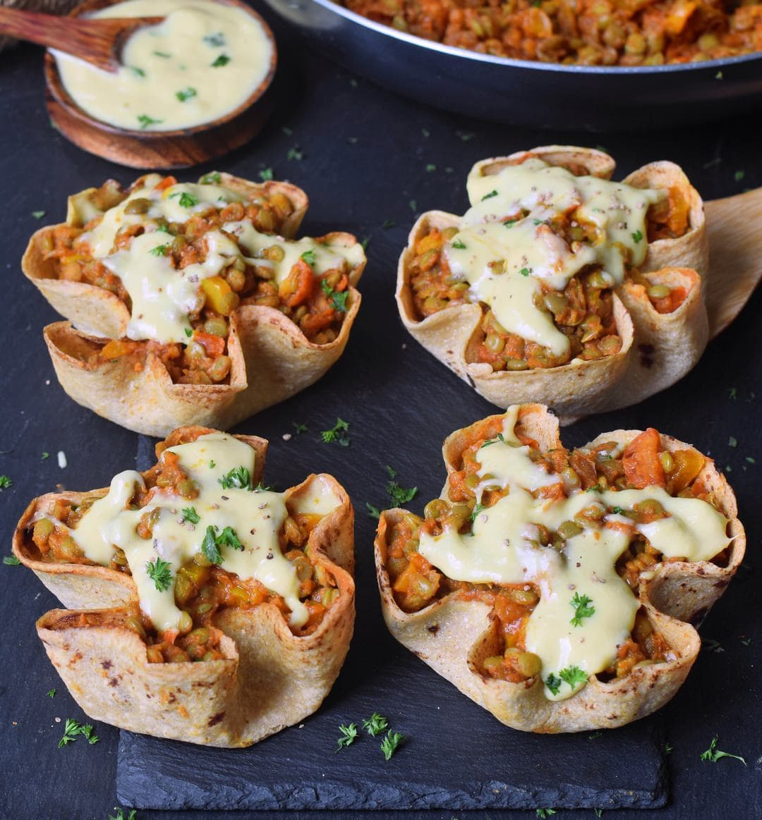 4 homemade easy tortilla bowls (taco cups) with lentils peppers tomatoes and vegan cheese sauce