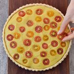 decorating vegan quiche with tomatoes