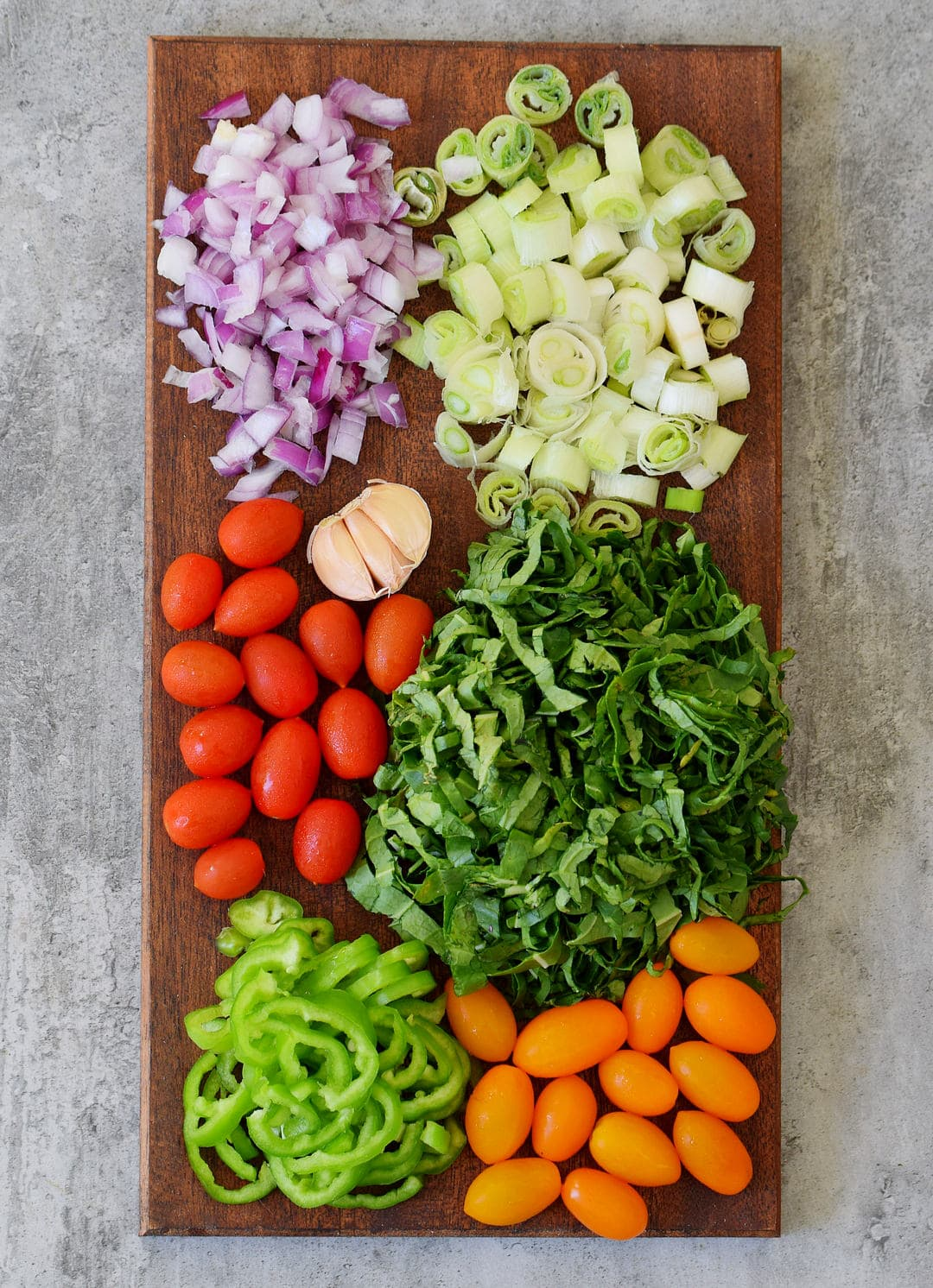 raw veggies like onion, cherry tomatoes, leeks, spinach, peppers on a brown wooden board