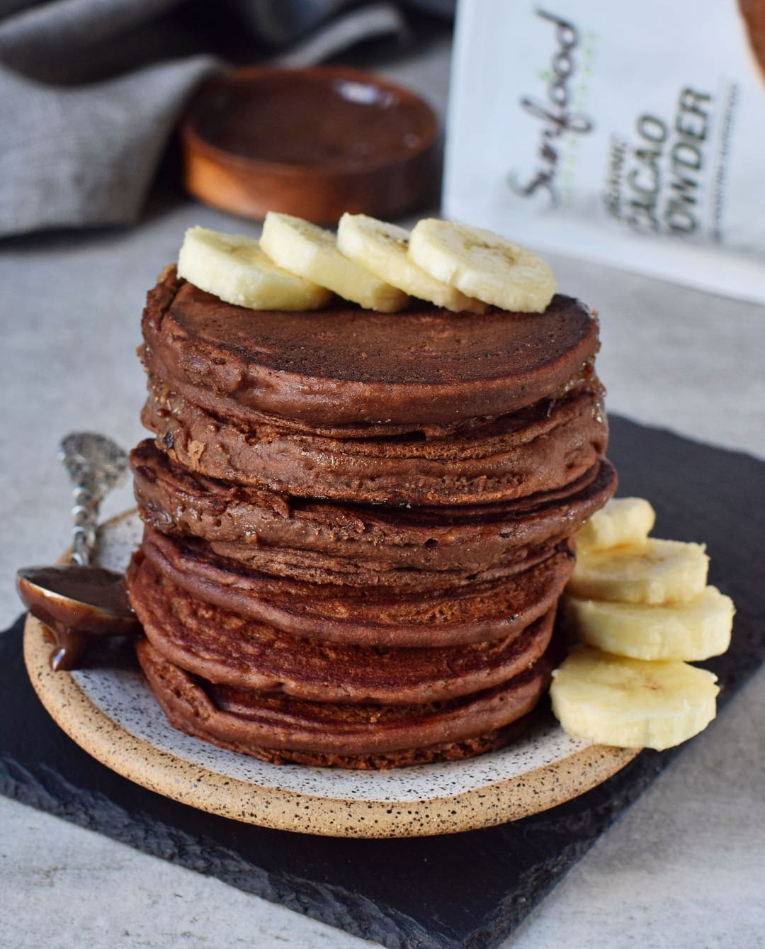 Gluten-free caramel chocolate pancakes with banana slices and Sunfood pouch in the background