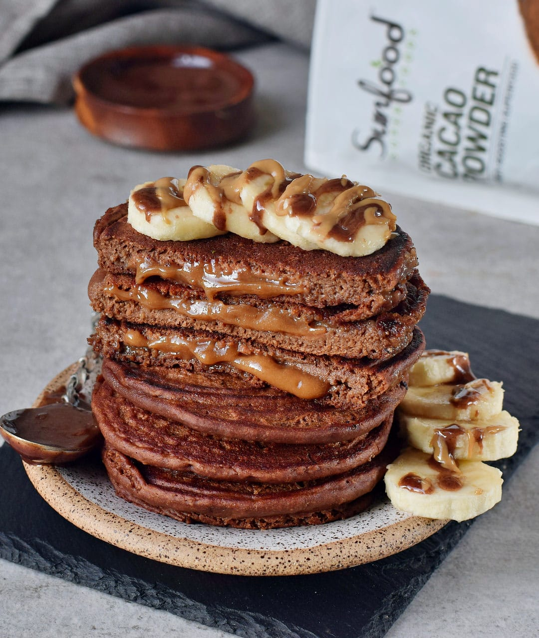 Vegan caramel chocolate pancakes with banana slices and Sunfood pouch in the background