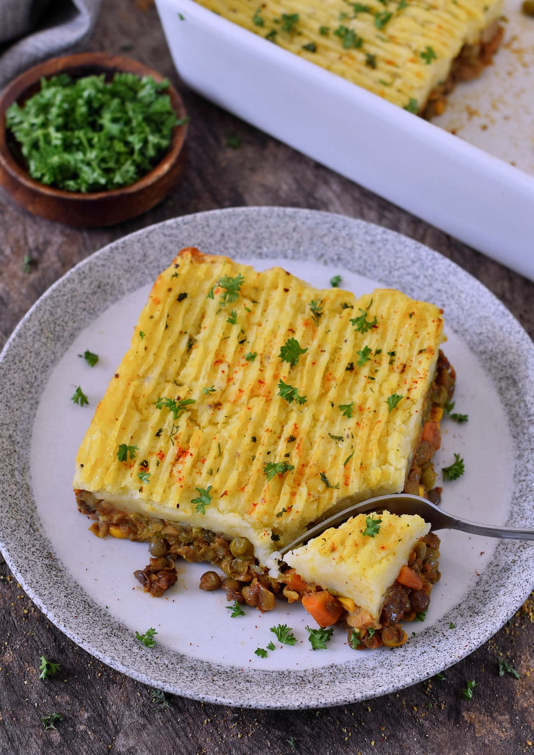 piece of a vegan shepherds pie on a plate with a fork