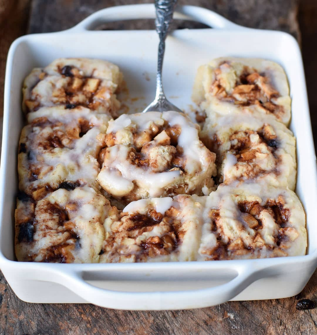 8 apple cinnamon rolls in a baking dish with icing sugar after baking