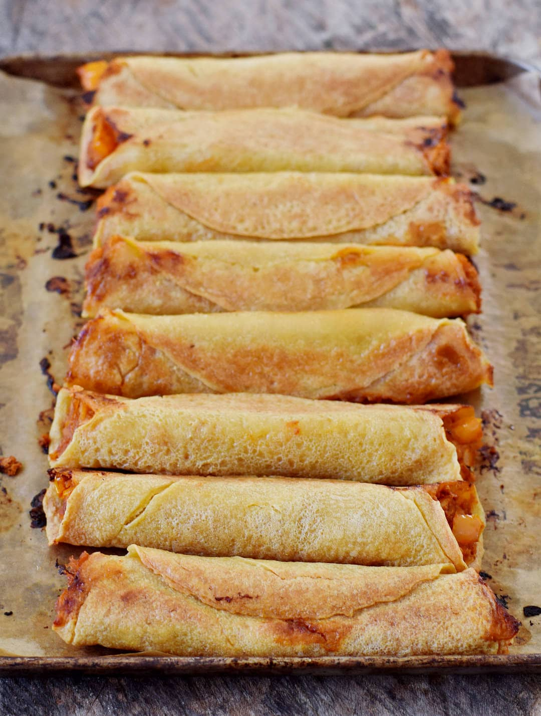 Baked Buffalo chickpea taquitos on a baking sheet in a row