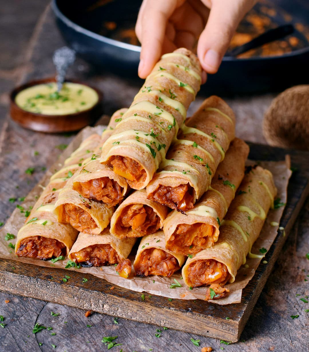 Hand grabbing Baked Buffalo chickpea taquitos with vegan cheese drizzle