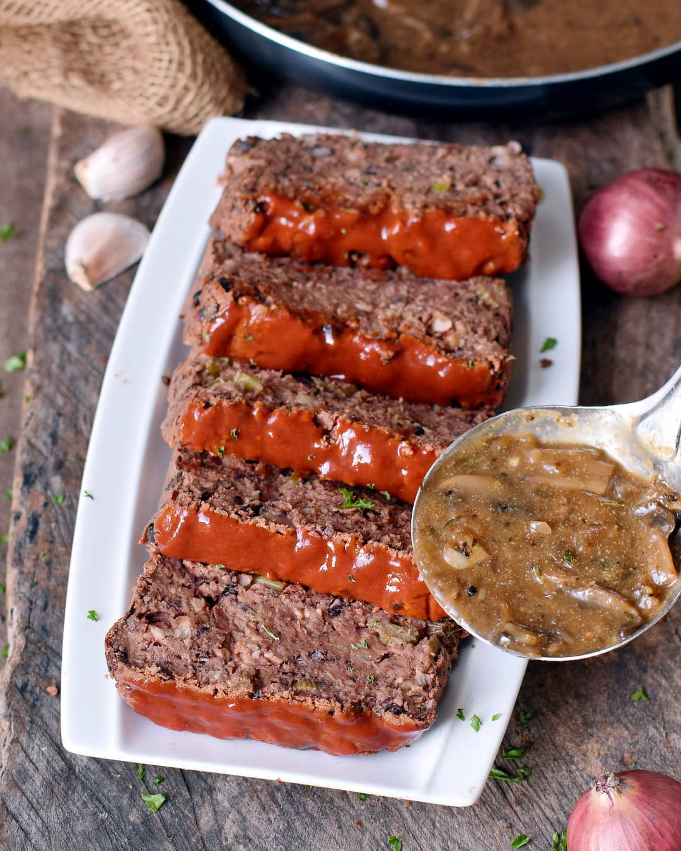 Veganer Braten (fleischloser Hackbraten) mit Pilzsoße auf weißem Teller