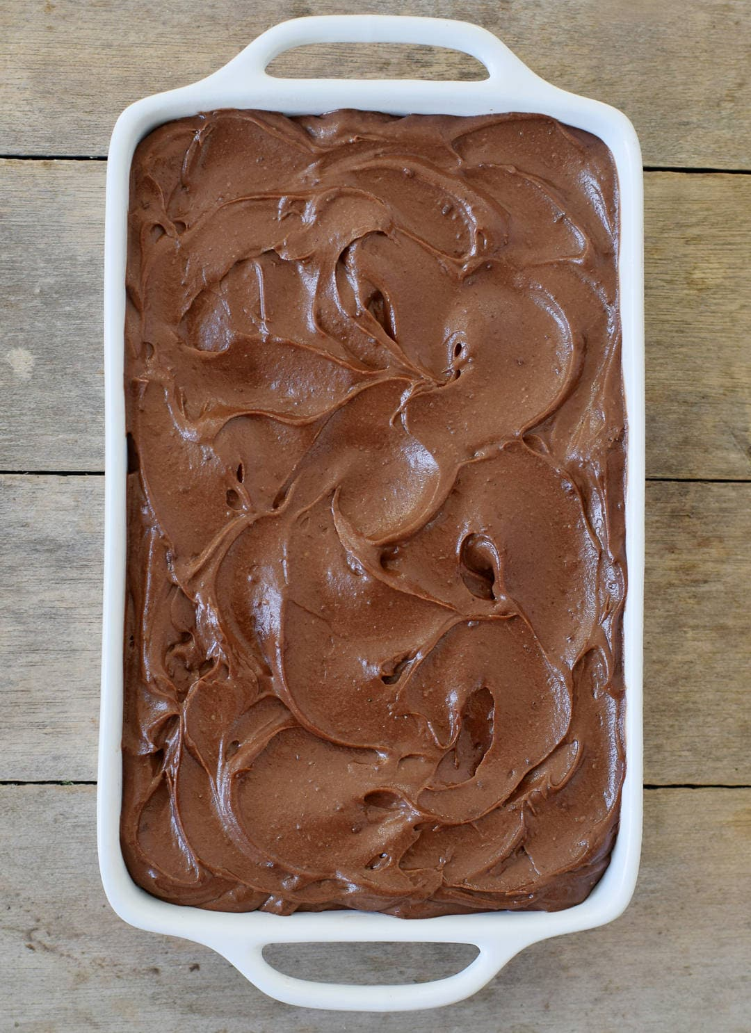 Chocolate batter in a baking dish with sweet potato frosting