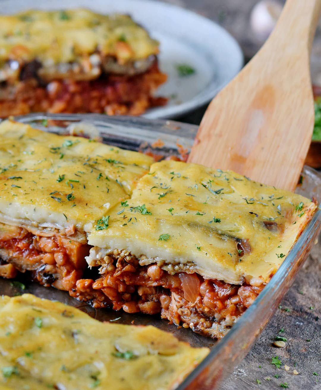 close-up of vegan moussaka and wooden spatula in a glass baking dish