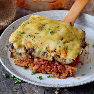 gluten-free vegan moussaka on a plate with a wooden spatula 320x320