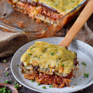 gluten-free vegan moussaka on a plate with a wooden spatula