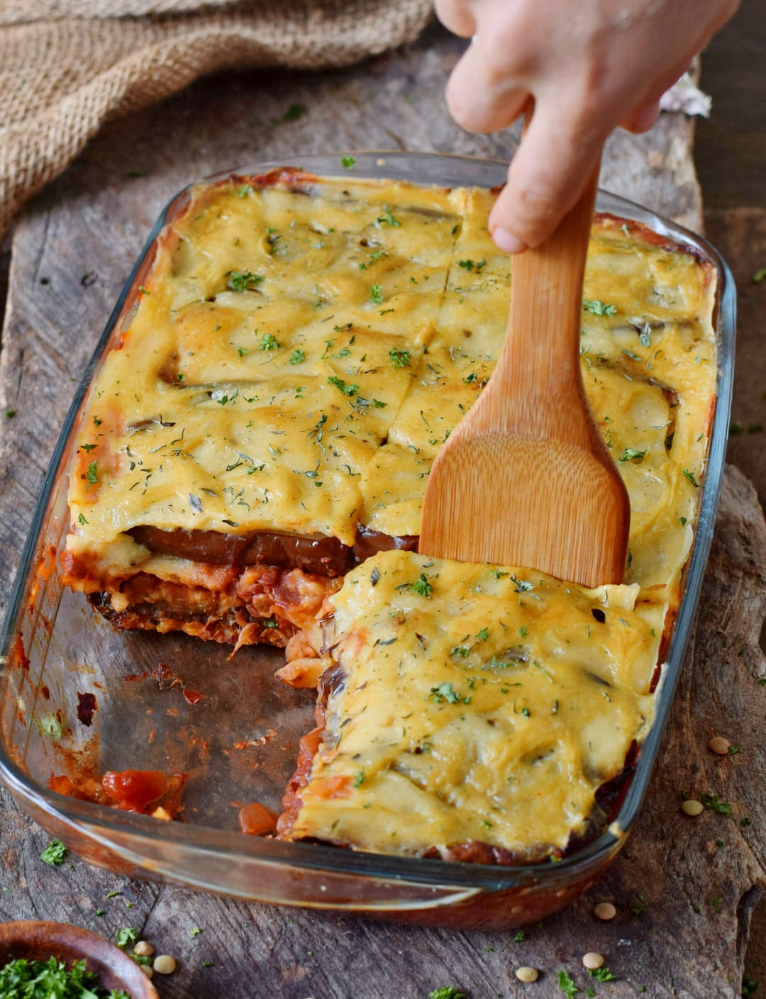 vegan moussaka and wooden spatula in a glass baking dish