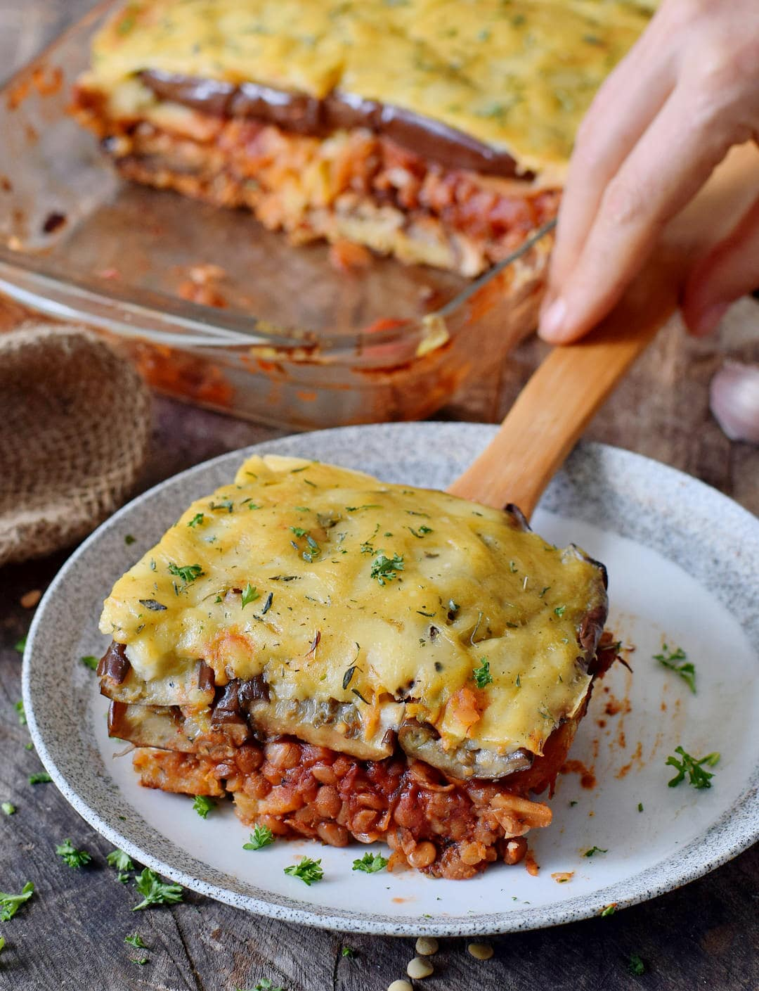vegan moussaka on a plate with a hand grabbing a wooden spatula