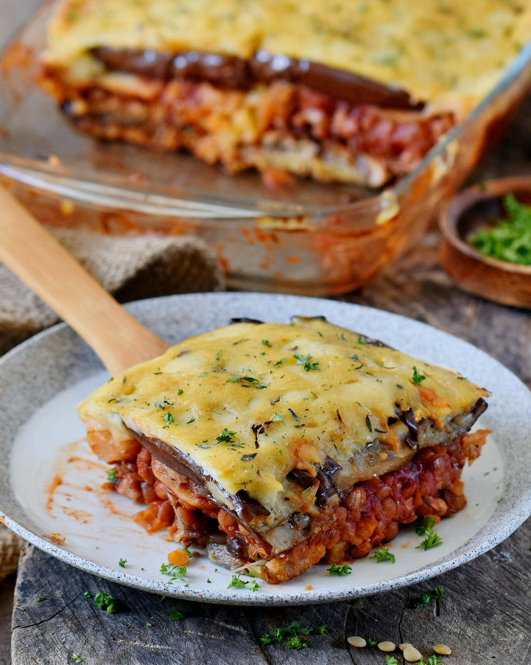 vegan moussaka on a plate with a wooden spatula