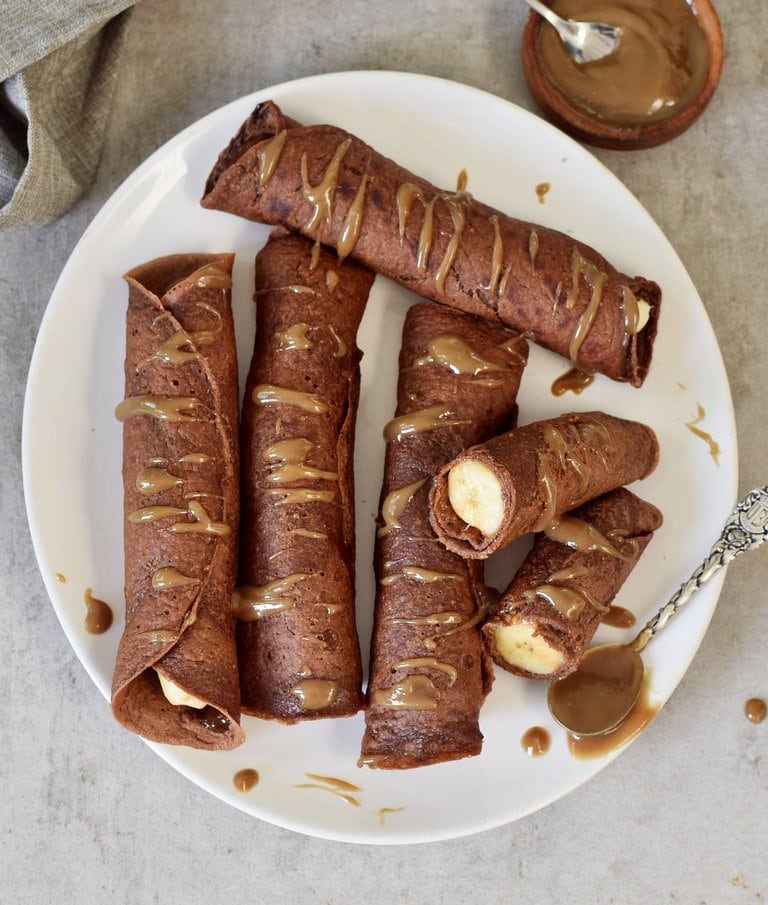 cutting banana stuffed chocolate crepes