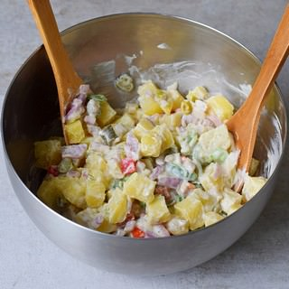 Creamy salad with dill pickles peppers and potatoes in a silver bowl