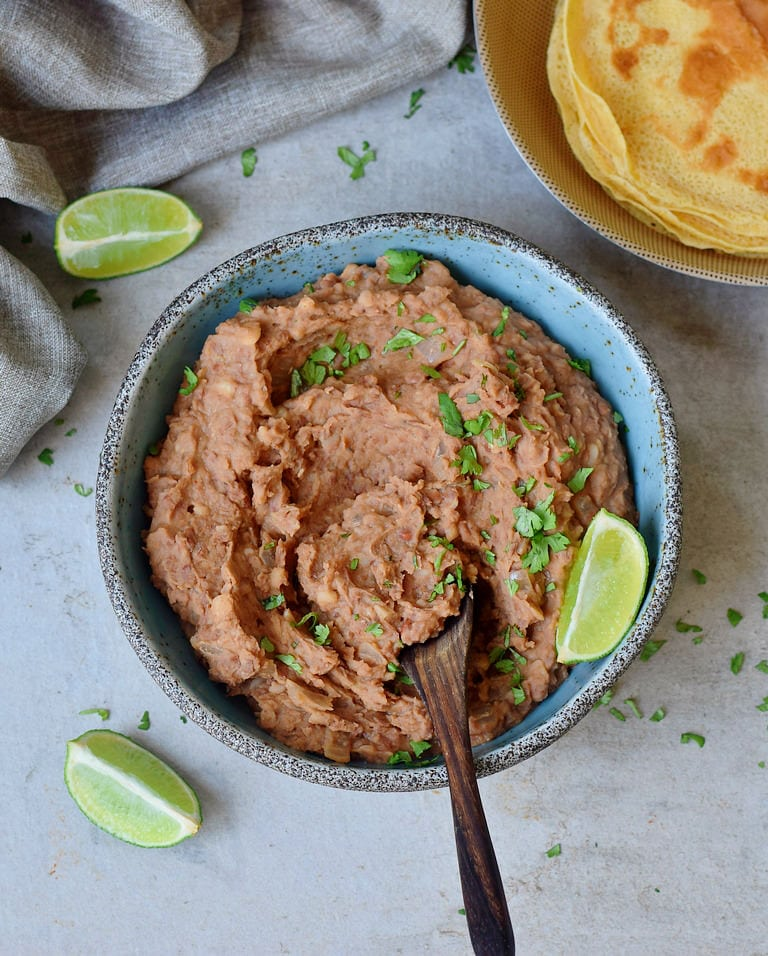 Instant Pot Refried Beans in a blue bowl with tortillas