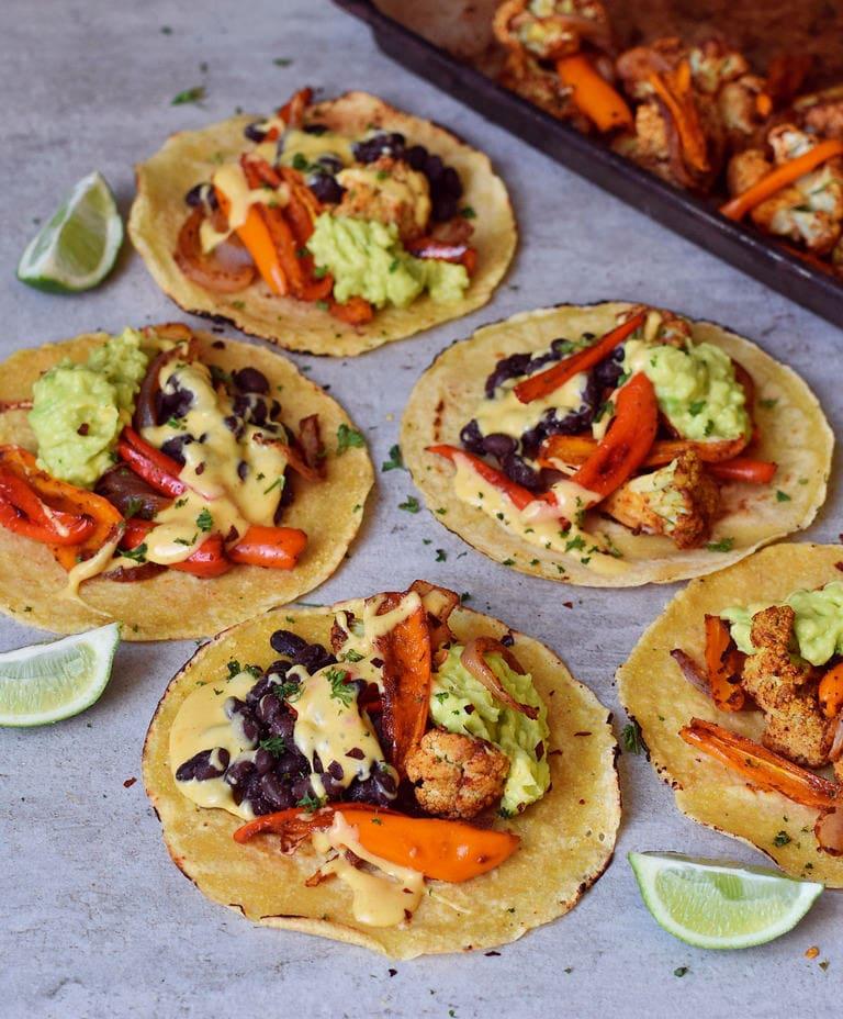 Selbstgemachte glutenfreie Tortillas mit geröstetem Blumenkohl, schwarzen Bohnen, Guacamole, Paprikas und veganem Käse