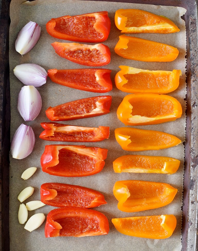 Baking sheet with red and orange peppers onion and garlic