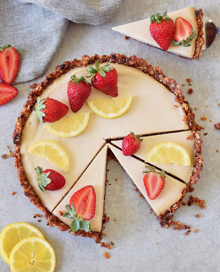 Gluten-free lemon cheesecake tart with granola crust strawberries and lemon slices