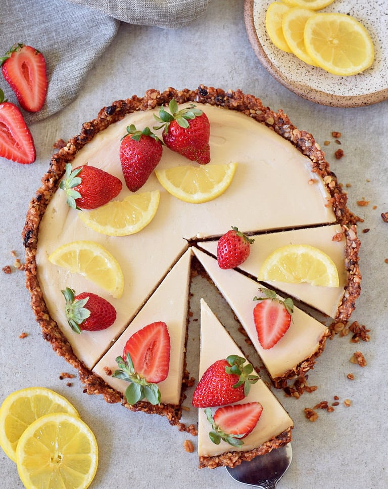 Vegan lemon cheesecake tart with granola crust and strawberries