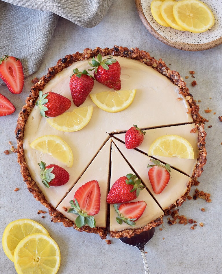Vegan cake with granola crust decorated with strawberries and lemon slices