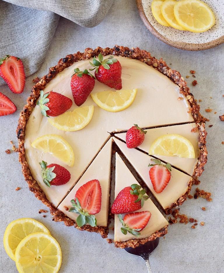 Zitronen Käsekuchen Tarte mit Müsliboden dekoriert mit Erdbeeren und Zitronenscheiben
