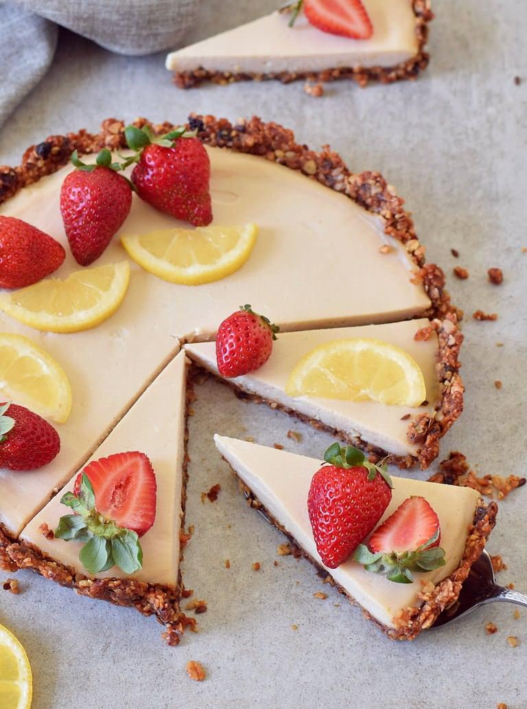 Glutenfreie Zitronen Käsekuchen Tarte mit Müsliboden dekoriert mit Erdbeeren und Zitronenscheiben